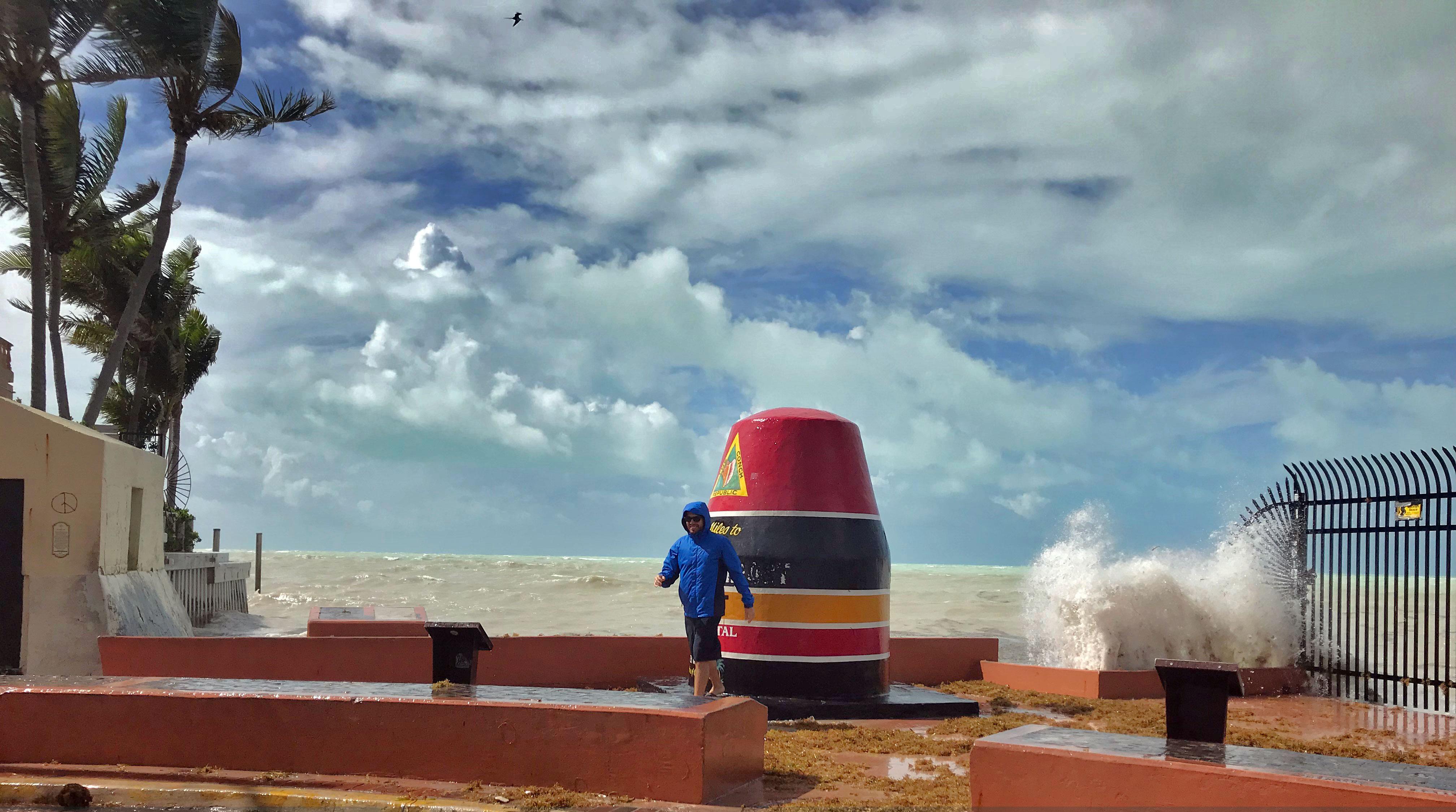 Man on the beach of key west wearing a rain coat before it starts to rain